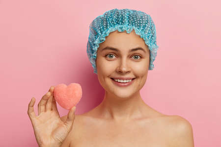 Headshot of cheerful European woman with happy expression, gentle smile, perfect teeth, wears shower cap, holds little heart shaped sponge, gets shower, has clean healthy skin. Hygiene concept