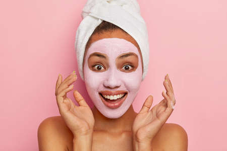 Headshot of optimistic young Afro American woman keeps hands near face, relaxes with facial mask, has toothy smile, poses with body, models against pink background. Natural beauty concept