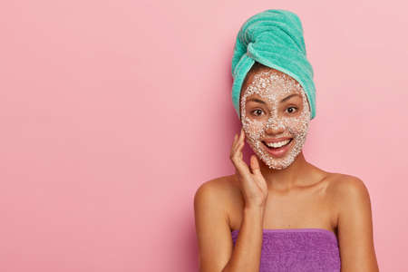 Horizontal shot of young woman cares about her skin, touches cheek with hand, takes shower and applies sea salt mask, models against pink studio background with copy space for your promotion