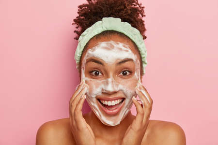 Image of glad dark skinned young female model has crisp hair, washes face with soap, cleans from pores, has problematic teenage skin, stands naked, wears headband, isolated over pink background Banco de Imagens