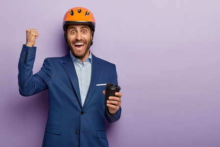 Photo of happy engineer has coffee break, holds paper cup, clenches fist with triumph, smiles gladfully, wears headgear and suit, isolated over purple wall with blank space aside. Occupation