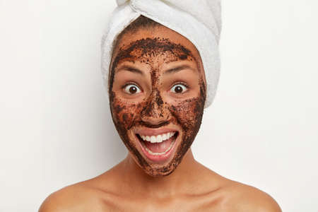 Beautiful joyous woman with healthy fresh skin, smiles broadly, looks with happy surprised reaction, applies coffee scrub facial mask for reducing dark dotes on skin, has spa therapy after shower