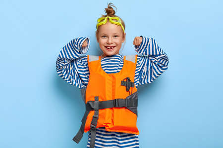 Pleasant looking redhaired girl in loose striped sailor jumper, raises arms, shows her strength, pretends being lifesaver at sea, wears protective goggles and inflated lifevest demonstrates power Banque d'images