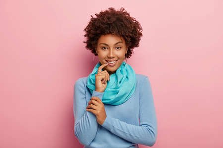 Half length shot of adorable Afro American woman with crisp hair, wears blue jumper with silk scarf keeps finger near lips, looks mysteriously at camera isolated over pink background. Emotions concept