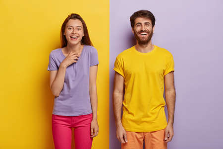 Photo of two delighted young woman and man stand together, express good emotions, smile happily, spend free time together, have fun, pose against yellow and purple background, dressed casually
