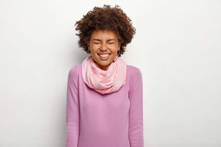 Overjoyed dark skinned woman keeps eyes closed, laughs happily, wears purple turtleneck with silk scarf, has broad smile, isolated over white background, feels upbeat, chills indoor, has fun