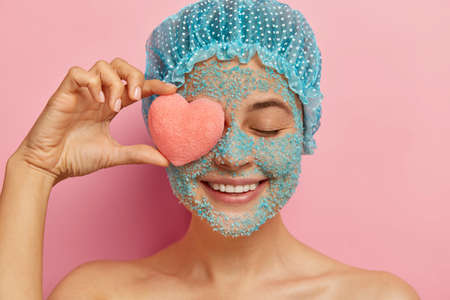Headshot of cheerful young woman with crystal sea salt scrub, holds pink heart shaped sponge on eye, smiles positively, wears showercap, models against pink background, peels face from pores
