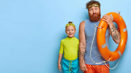Photo of confused bearded ginger man dressed in sailor vest, holds orange inflated lifebuoy, small child in t shirt and shorts, holds hand of affectionate father, wears goggles for swimming.
