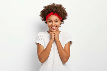 Portrait of pretty young African American woman holds hands under chin, smiles happily, dressed in casual wear, enjoys nice day with family, poses over white background. Curly pleased girl feels good Standard-Bild