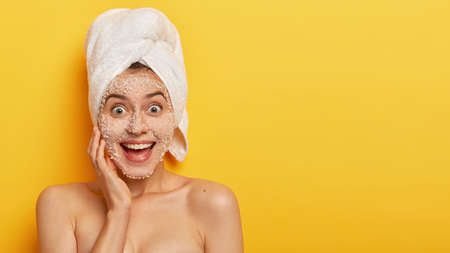 Glad young woman with peel off mask, has sensitive skin, smiles broadly, shows white teeth, gazes happily, enjoys freshness on her complexion, wears white towel on head, models indoor shirtless
