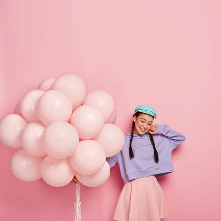Vertical shot of pleased brunette woman with two braids, wears stylish cap, purple loose sweatshirt and rosy skirt, holds helium balloons, celebrates birthday in merry company, poses for making photo