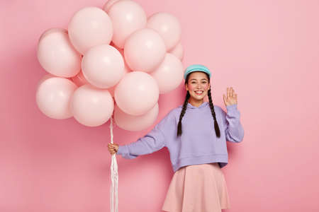 Positive Chinese woman comes on friends birthday party, greets fellows, has dark hair combed in two plaits, dressed in casual outfit, holds helium balloons, poses over pink studio wall
