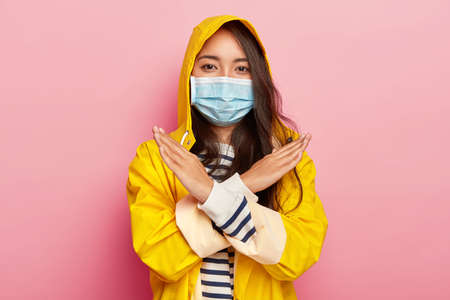 Serious Asian girl makes stop or ban gesture, has infectious disease, keeps arms crossed, wears waterproof raincoat, poses indoor against pink background. Woman with medical mask on mouth and nose