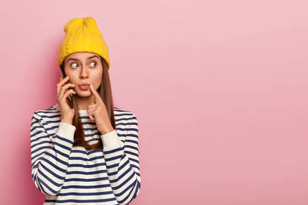 Photo of surprised young European woman looks surprisingly aside, keeps mobile phone near ear, has telephone conversation, looks away, wears fashionable outfit, isolated over pink wall, blank space