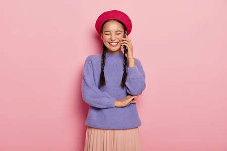 Overjoyed pleased woman with Asian appearance, enjoys funny telephone conversation with friend, keeps modern cellular near ear, has two long pigtails, poses in studio over pink wall. Communication