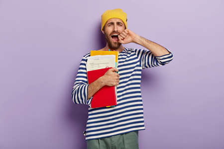 Photo of dissatisfied unshaven young man yawns from tiredness, being sleepy and exhausted, keeps hand near opened mouth, holds papers with notepad and textbook, isolated over purple background