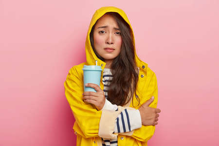 Photo of dissatisfied Asian woman smirks face, keeps arms crossed, trembles from being cold after walking in rain, wears yellow raincoat, holds takeaway coffee, warms herself with hot beverage