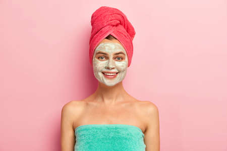 Smiling happy young woman applies nourishing homemade clay mask on face, pampers skin, wrapped in soft towel, cares about complexion, has natural beauty, models indoor. Purity and beauty concept