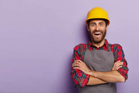 Positive happy foreman in workwear, keeps arms folded, wears yellow hardhat, receives new task from boss, glad to be promoted, stands against purple background, blank free space. Repairman indoor