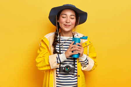 People and tourism concept. Satisfied attractive female with pigtail, drinks hot coffee or tea from flask, wears casual waterproof clothes, retro camera hanging on neck, likes adventures and traveling