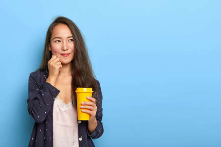 Pleased lovely brunette Asian woman has dreamy face expression, thinks what to do this day, awakes early, drinks refreshed coffee, dressed in pyjamas, blank space on right. Sensual girl in nightwear Stock Photo