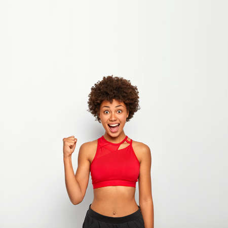 Vertical image of joyful African American woman raises clenched fist, cheers for something, gestures with triumph, has perfect figure, wears red top, poses against white background, blank space above