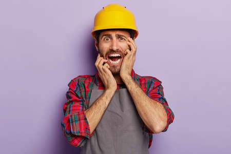 Panicking male architect looks stressfully, worries to have deadline, dressed in special uniform, yellow hardhat, has stubble, poses on purple background. People, occupation, negative emotions concept