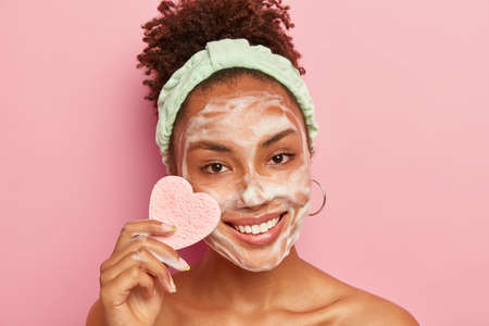 Portrait of happy ethnic woman has perfect well cared skin, applies foaming soap for washing face, has pleased expression, holds heart shaped sponge for wiping makeup, looks gladfully at camera Banco de Imagens