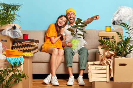 Happy dark haired girl leans at shoulder of boyfriend who holds wrapped potted domestic plant, points into distance with index finger, remove in new house, rent flat for cheap price, have moving day