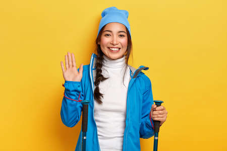 Photo of cheerful Asain female traveler holds hiking equipment, waves palm, greets friend in mountains, being active hiker, smiles pleasantly, isolated over yellow background. Trekking, camping Stock fotó