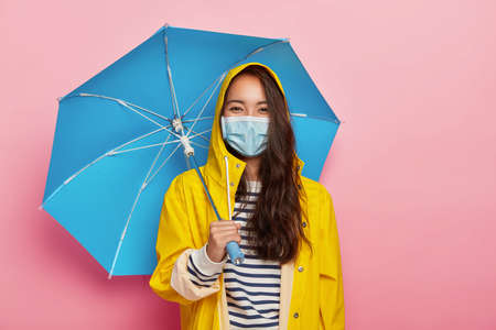 Photo of Asian woman wears protective mask, faces air pollution during rainy day, stands under umbrella, dressed in yellow raincoat, isolated on pink background. Acid rain and dirty environment