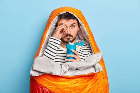 Image of fatigue unshaven male rubs eyes, has sleepy expression, camping travel, relaxes in sleeping bag, enjoys adventure weekend, has flask in hand, drinks tea, being in harmony with nature