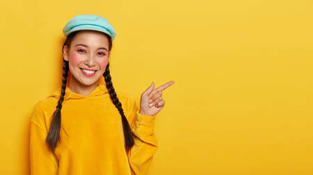 Friendly looking cheerful Asian woman points fore finger aside, recommends cool advertisement, has two braids, wears stylish cap and yellow sweatshirt, sure you will like it, suggests buying something Stock fotó