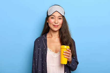 Satisfied young female wears sleeping mask and nightwear, tries to refresh with aromatic takeaway coffee, enjoys time for rest, poses against blue studio wall. People, bedding, morning time concept