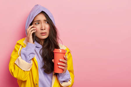 Displeased Asian woman with rosy cheeks, has nervous face expression, calls boyfriend via smartphone, tries to warm herself with takeaway coffee, wears yellow raincoat and hood, poses indoor 版權商用圖片