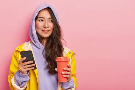 Pretty brunette young woman with natural beauty, uses modern cellphone for chatting with friends, holds takeaway coffee, isolated over pink background. People, technolgy and lifestyle concept