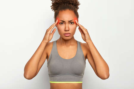 Image of serious black woman touches both temples, suffers from migraine, wears grey top, has red marked zones on head showing painful area, looks tensed and tired, isolated over white background Stock fotó
