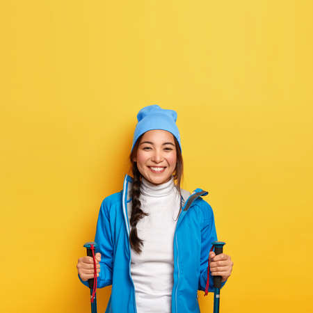 Vertical image of happy active Asian female stands with trekking poles, wears blue hat and jacket, being on mountain trail, hikes during autumn vacation in forest, isolated over yellow background