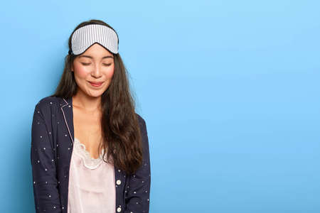 Half length shot of satisfied Korean girl prepares for sleep in bedroom, wears sleeping mask, casual pyjamas, focused down with pleasure, enjoys good rest, isolated over blue background. Rest concept