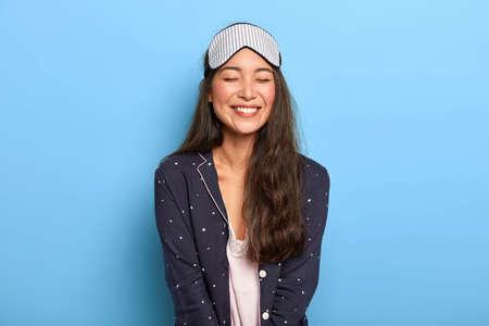 Indoor shot of cheerful woman with pleasant toothy smile, wears comfortable pyjamas and sleep mask, enjoys bedtime routine, smiles broadly at camera, poses in studio against blue studio wall Imagens