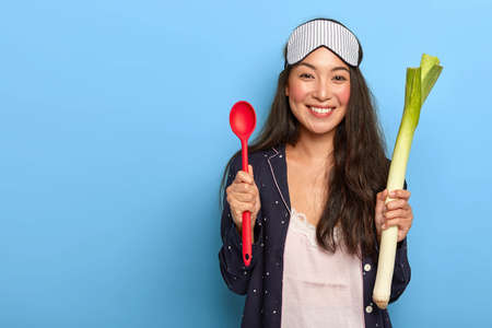 Photo of happy housewife going to cook healthy dish in morning, holds green leek and red spoon, smiles pleasantly, wears nightclothes, sleeping mask, stands against blue background. Culinary concept Stock fotó