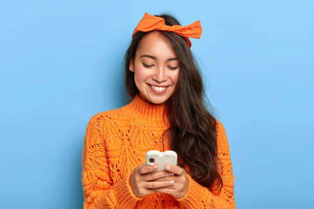 Photo of stylish brunette millennial girl busy checking her email box, holds mobile phone, wears orange headband tied in bow, warm sweater, connected to wireless internet, gets pleasant message Stock fotó