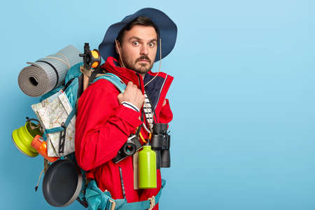 Photo of male vacationist has active rest, carries rucksack with map, rolled up rag, wears casual tourist clothes, uses binoculars, flask with hot drink surprised by something. Backpacking concept 版權商用圖片