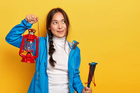 Indoor shot of pretty Asian woman holds oil lamp, looks thoughtfully aside, holds trekking poles and kerosene lamp, has rest in camp near forest poses over yellow wall. People, lifestyle, rest concept