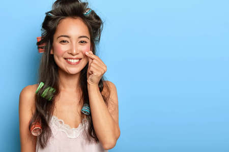Lovely brunette Asian woman makes love sign, shapes little heart with fingers, smiles positively, dressed in nightwear, makes hairstyle with curlers, poses against blue wall, empty space for promo