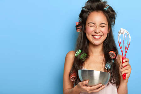 Overjoyed busy wife whisks cream in bowl to perfect peaks, has pleased face expression, dressed in nightwear, poses against blue studio wall, free space for your promotion, holds beater indoor