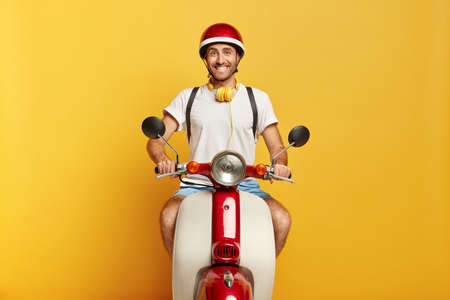 Image of positive male rides scooter on road through city, wears helmet, white t shirt, being in good mood, enjoys adventurous trip, transports something in rucksack, isolated over yellow studio wall