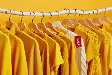 Black Friday and discounts concept. Yellow and white clothes on sale hangings on racks against vivid background. Big sale and shopping. Stylish outfits for women in home closet or shopping mall Stockfoto