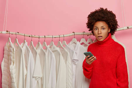Embarrassed Afro American woman uses mobile phone for purchasing, poses in clothing store, wears red sweater, poses near rack with white clothing, afraids of spending much money for clothes. Stockfoto