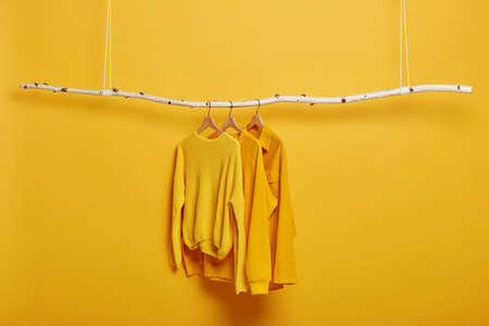 Selective focus. Three items of clothes on hangers. Long sleeved yellow jumpers on wooden rack near bright vivid wall. Copy space for text. Various casual outfits hanging in row at dressing room Stockfoto